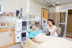Worried Woman Looking At Critical Patient. Worried young women looking at critical patient in hospital stock photography