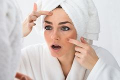 Worried woman looking at pimple on face Stock Images