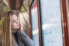 Worried woman looking at train timetable Royalty Free Stock Photos
