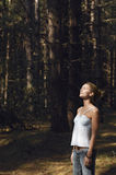Worried Woman Looking Up In Woods Stock Photography