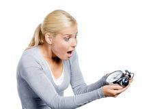 Worried woman looks at the alarm clock Stock Photos