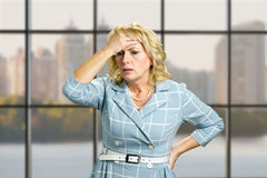 Worried woman on office background. Stressed busineswoman with headache, migraine or forgetfulness on office window background Royalty Free Stock Photo