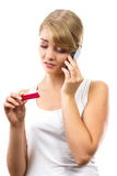Worried woman with phone informing someone about positive pregnancy test Royalty Free Stock Image