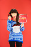 Worried woman on phone with naughty sign. Shocked woman in ugly Santa sweater holding phone and naughty sign over red background Stock Photo