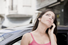 Worried woman on the phone. Worried young woman in car talking on the phone Stock Photo