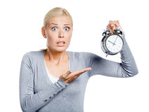 Worried woman pointing at the alarm clock Stock Photography