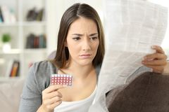 Worried woman reading contraceptive pills leaflet. Sitting on a couch at home royalty free stock photo