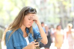 Worried woman reading phone content in the street. Worried woman reading online smart phone content in the street Royalty Free Stock Images