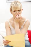 Worried woman's reading letter. Stock Photo