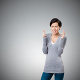 Worried woman shows crossed fingers Royalty Free Stock Photography