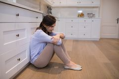 Worried woman sitting in kitchen royalty free stock photo