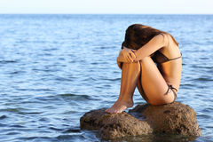 Worried woman sitting on a rock on the beach Stock Images