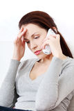 Worried woman sitting on a sofa on a phone. Royalty Free Stock Images