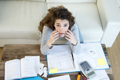 Worried woman suffering stress doing domestic accounting paperwork bills and invoices. View from above of woman suffering stress doing domestic accounting Stock Photography