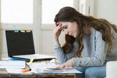Worried woman suffering stress doing domestic accounting paperwork bills and invoices. Young attractive and desperate woman suffering stress doing domestic Royalty Free Stock Photo