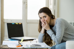 Worried woman suffering stress doing domestic accounting paperwork bills and invoices. Young attractive and desperate woman suffering stress doing domestic Royalty Free Stock Photos