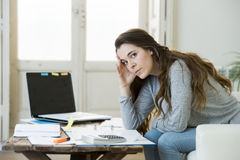 Worried woman suffering stress doing domestic accounting paperwork bills and invoices. Young attractive and desperate woman suffering stress doing domestic Stock Photography