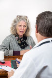 Worried Woman Talking with Her Doctor Royalty Free Stock Photos