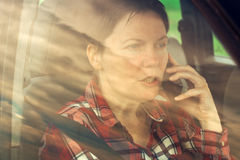 Worried woman talking on mobile phone in car Royalty Free Stock Photography