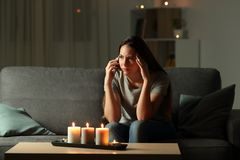 Worried woman talking on phone during blackout. Sitting on a couch in the living room at home Stock Images