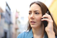 Worried woman talking on phone walking in the street royalty free stock photography