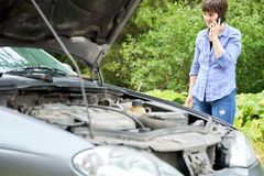 Worried woman talks on the phone near her old broken car. Worried middle-aged woman talks on the phone near her old broken car with raised hood royalty free stock images