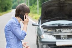 Worried woman talks on the phone near her old broken car on the road. Worried middle-aged woman talks on the phone near her old broken car with raised hood on stock photos