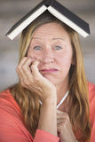 Worried woman thinking with book on head Stock Image