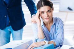 Worried woman touching her forehead while having a headache at work. Headache again. Young tired emotional women feeling unwell and having a headache while Royalty Free Stock Photo