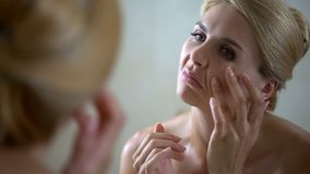 Worried woman trying to smooth wrinkles, face lifting, plastic surgery concept royalty free stock photography
