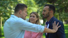 Worried woman trying to stop jealous boyfriend fighting with another man. Stock footage stock video footage