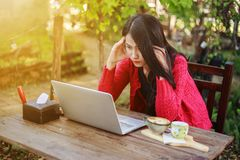 Worried woman using laptop and drinking coffee in garden stock photos