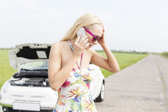 Worried woman using mobile phone on country road with broken down car in background Stock Image