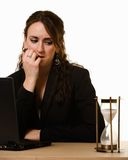 Worried woman Watching the clock. Attractive young brunette woman in business suit working at desk in front of laptop looking over at a hour glass with worried Stock Photo