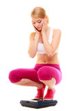 Worried woman weighing scale. Slimming weight loss. Stock Photo