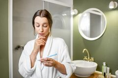 Worried woman wiwth pregnancy test in the bathroom stock image