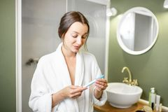 Worried woman wiwth pregnancy test in the bathroom royalty free stock images