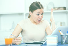 Worried woman working on laptop. Portrait of sad and worried woman working on laptop Royalty Free Stock Photo
