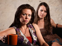 Worried Women Sitting. Serious pair of Caucasian brunette females sitting together Stock Photography