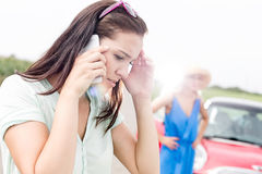 Worried woman using mobile phone while friend standing by broken down car on sunny day. Worried women using mobile phone while friend standing by broken down car royalty free stock image