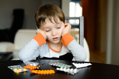 Worried 4 year old boy sitting at the table with medications Stock Photography