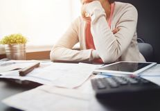 Worried young Asian woman calculating her monthly expenses. Stressed Female thinking something at her house. Financial problems concept Stock Image