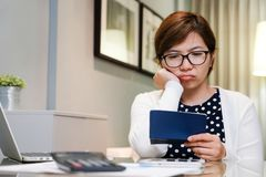 Worried young Asian woman calculating her monthly expenses. Stressed Female thinking something at her house. Financial problems concept Stock Photography
