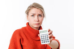 Worried young blond woman pouting, holding a calculator, losing money stock images