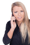 Worried young blond woman talking on mobile phone Royalty Free Stock Photo