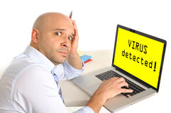 Worried young business man at computer infected with virus. Worried frustrated young business man at computer infected with virus Royalty Free Stock Image