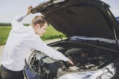 Free Worried Young Businessman Examining Broken Car Royalty Free Stock Images - 123131749