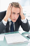 Worried young businessman at office desk Royalty Free Stock Photos
