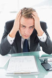 Worried young businessman at office desk Stock Photo