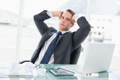 Worried young businessman sitting at office desk Stock Photography